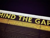 a wooden sign featuring the words mind the gap