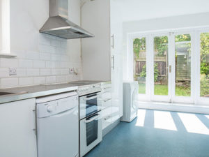 white kitchen with doors to garden; To let