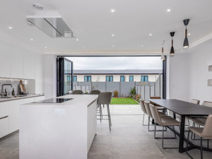 Large white open plan kitchen extension, doors open to garden