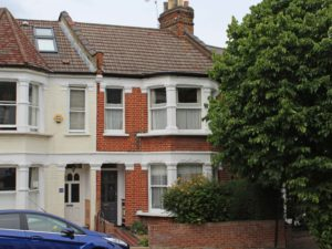 Red brick Victorian house with low wall and tree