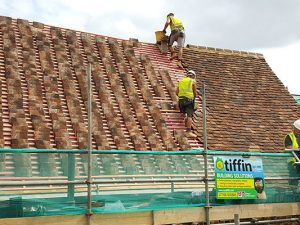 Two men working on a tile roof