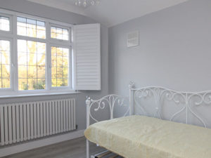 Bedroom with daybed and open shutters