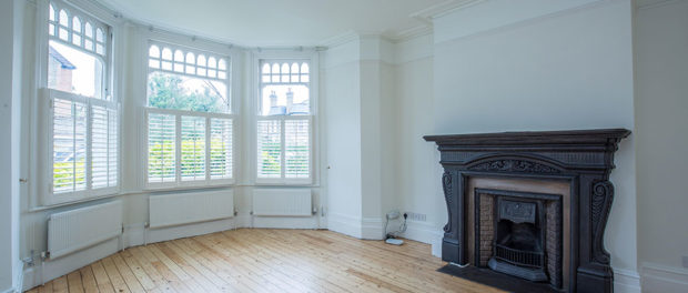 Large living room with wooden floors, fireplace and 3 sets of windows