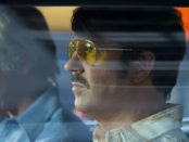 2 male actors seen through car window