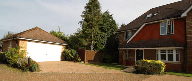 External view of large house with big driveway, trees and garage with white door at rear