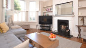 Photo of bright airy furnished lounge with fireplace and bay window