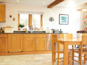 Picture of a big airy light kitchen with wooden units and kitchen table with chairs
