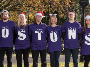 Team at Mostons wearing purple tops spelling word MOSTONS