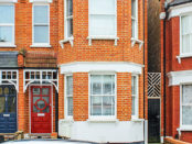 Street view of semi-detached bay fronted Edwardian red bricked house