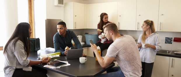 5 students relaxing in kitchen