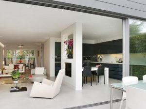 Huge openplay living with white lounge to left and black kitchen to right. Large glass doors open with outside table in foreground.
