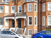 Streetview of brick Victorian property with cars parked upfront