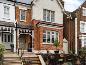 External view of brick Victorian house with steps to front door and pot plants