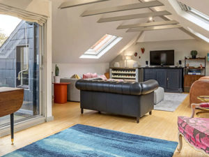 Open plan room with large glass doors, velux windows, lounge area